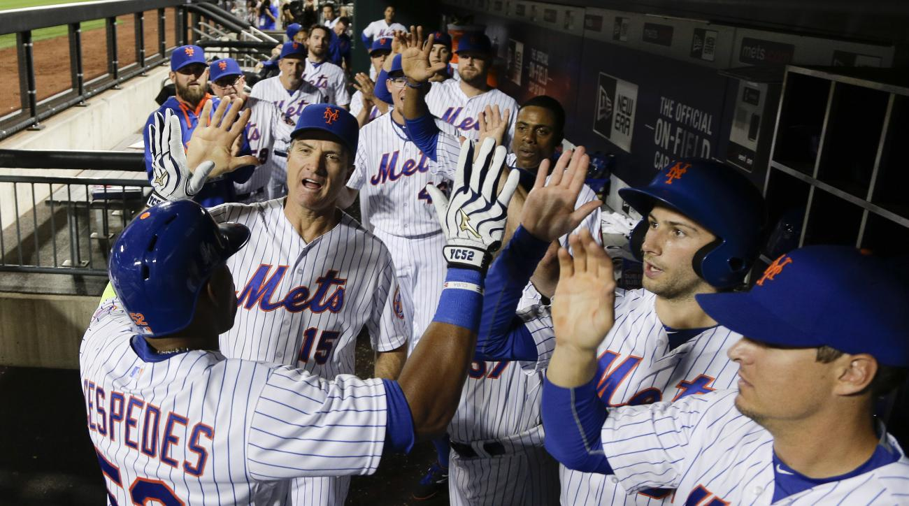New York Mets' Yoenis Cespedes, left, is greeted in the dugout by teammates after hitting a solo home run against the Colorado Rockies during the eighth inning of a baseball game, Wednesday, Aug. 12, 2015, in New York. (AP Photo/Julie Jacobson)