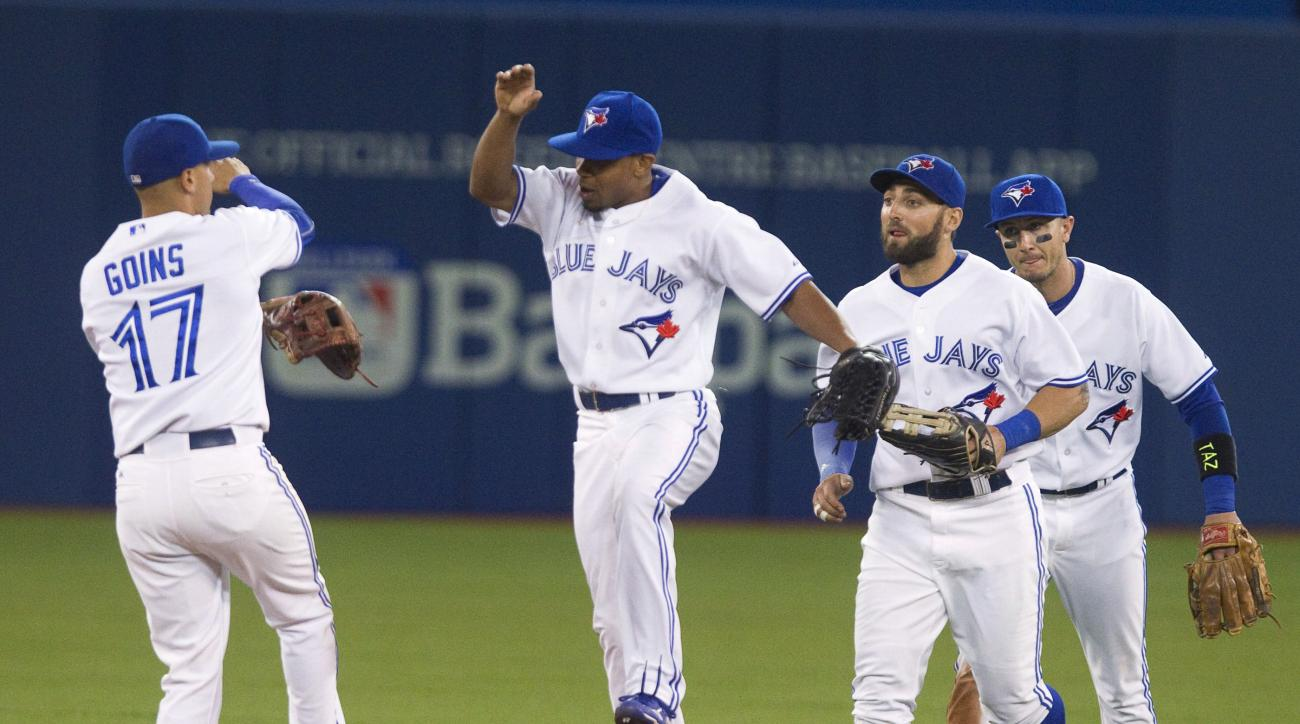 Toronto Blue Jays' Ryan Goins, Ben Revere, Kevin Pillar and Troy Tulowitzki, from left, celebrate after the Blue Jays defeated the Oakland Athletics 10-3 in a baseball game in Toronto on Wednesday, Aug. 12, 2015. (Fred Thornhill/The Canadian Press via AP