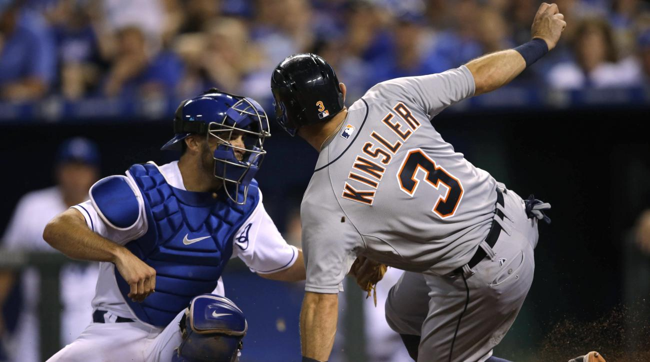 Detroit Tigers' Ian Kinsler (3) beats the tag by Kansas City Royals catcher Drew Butera, left, during the eighth inning of a baseball game at Kauffman Stadium in Kansas City, Mo., Wednesday, Aug. 12, 2015. Kinsler scored on a hit by Tyler Collins. (AP Pho