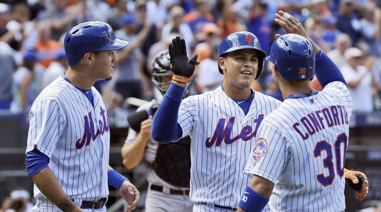 New York Mets' Juan Lagares, center, celebrates after hitting a three-run home run with teammates Michael Conforto, right, and Wilmer Flores during the eighth inning of a baseball game against the Colorado Rockies at Citi Field, Thursday, Aug. 13, 2015 in