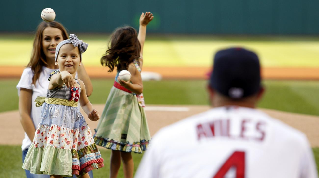Cleveland Indians' Mike Aviles catches the ceremonial first pitch from his daughter Adriana as his wife, Jessy, watches prior to the Indians' baseball game against the New York Yankees on Thursday, Aug.13, 2015, in Cleveland. (AP Photo/Aaron Josefczyk