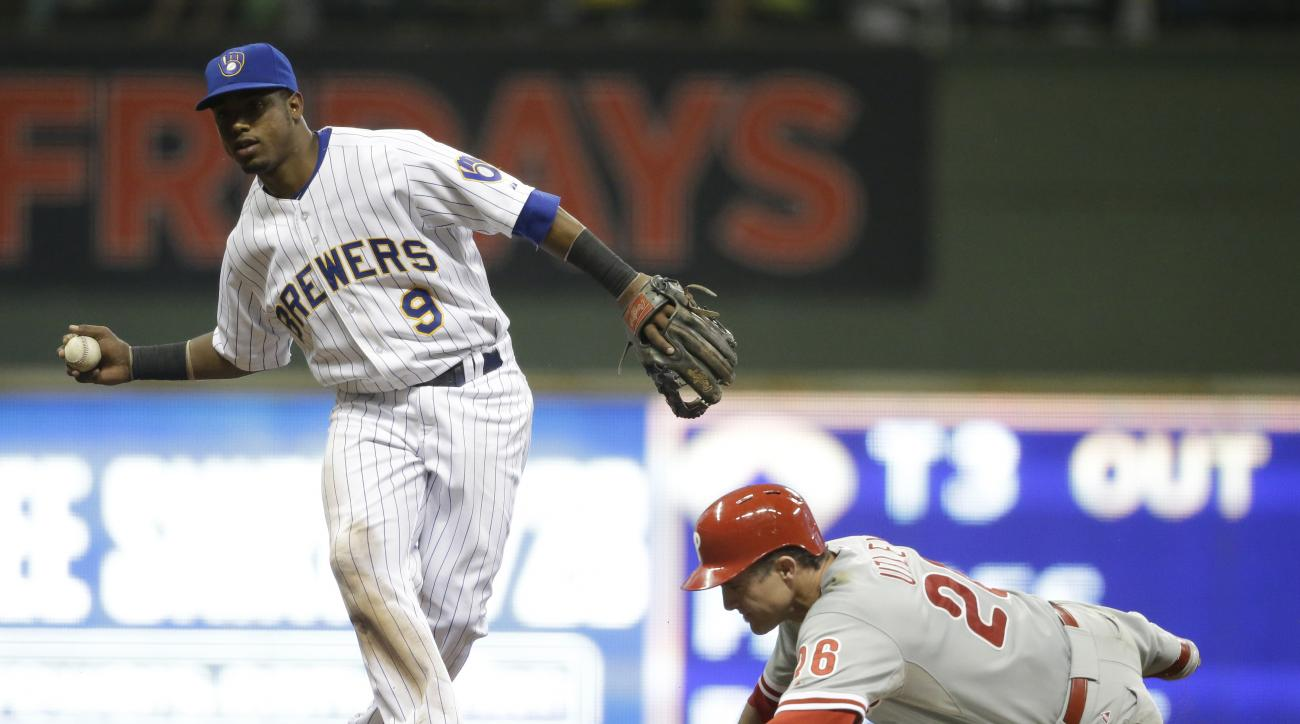Milwaukee Brewers' Jean Segura, left, forces out Philadelphia Phillies' Chase Utley, right, at second base during the fifth inning of a baseball game Friday, Aug. 14, 2015, in Milwaukee. (AP Photo/Jeffrey Phelps)
