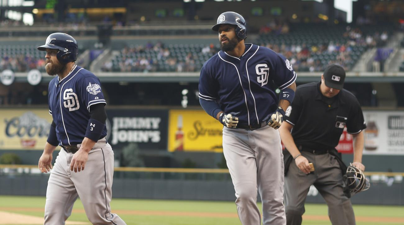 San Diego Padres' Matt Kemp, center, crosses home plate after hitting a two-run home run to drive in teammate Derek Norris, left, as home plate umpire Lance Barrett cleans off the plate against the Colorado Rockies in the first inning of a baseball game F