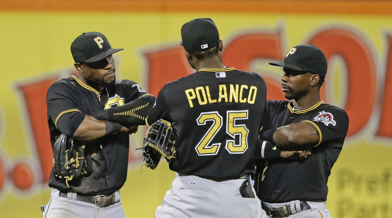 Pittsburgh Pirates' Starling Marte, left, and Andrew McCutchen, right, celebrate with Gregory Polanco after a baseball game against the New York Mets on Friday, Aug. 14, 2015, in New York. The Pirates won 3-2 in 10 innings. (AP Photo/Frank Franklin II)