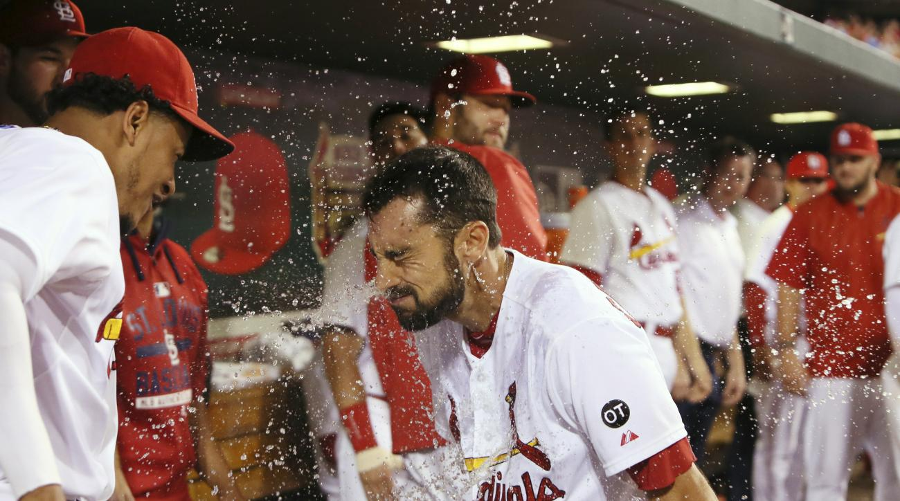 St. Louis Cardinals' Matt Carpenter is splashed with water by pitcher Carlos Martinez, left, after hitting a solo home run in eighth inning against the Miami Marlins in a baseball game Friday, Aug. 14, 2015, in St. Louis, The Cardinals won 3-1. (Chris Lee