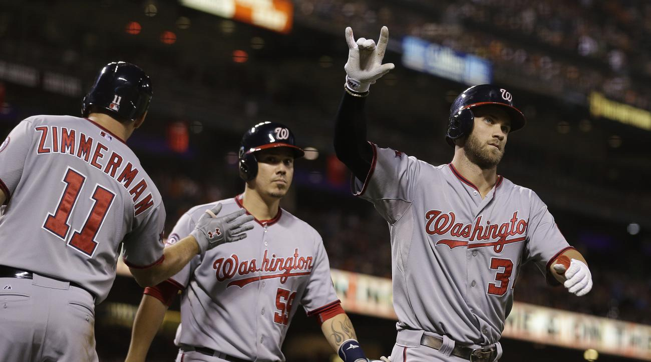 Washington Nationals' Bryce Harper, right, reacts after hitting a three-run home run off San Francisco Giants starting pitcher Matt Cain during the fifth inning of a baseball game Friday, Aug. 14, 2015, in San Francisco. At left are Nationals' Ryan Zimmer