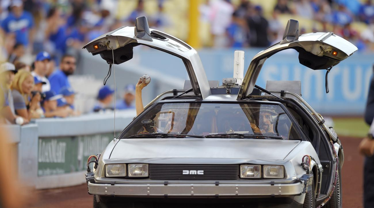 Actress Lea Thompson, left, rides onto the field in a customized DeLorean before throwing out the ceremonial first pitch prior to a baseball game between the Los Angeles Dodgers and the Cincinnati Reds, Saturday, Aug. 15, 2015, in Los Angeles. Thompson wa