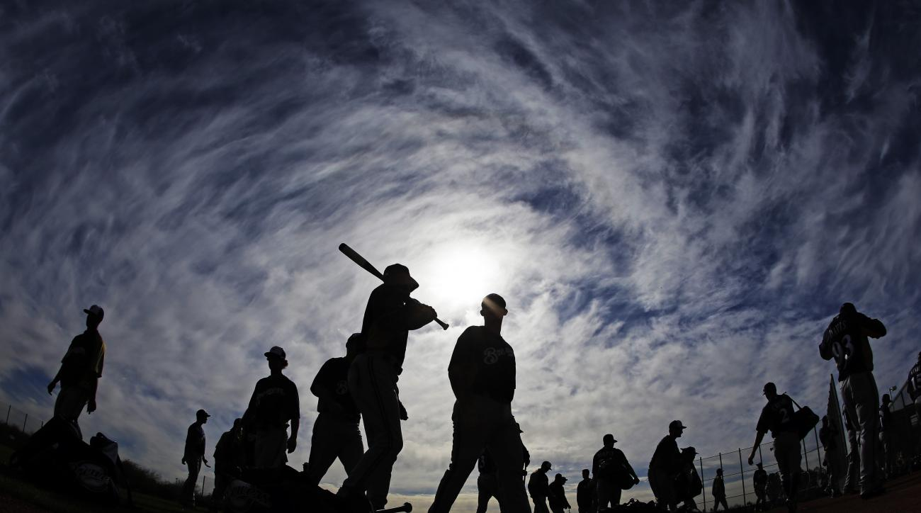 In this photo made with a fisheye lens, Milwaukee Brewers players make their way to a practice field during a spring training baseball workout Tuesday, Feb. 19, 2013, in Phoenix. (AP Photo/Morry Gash)