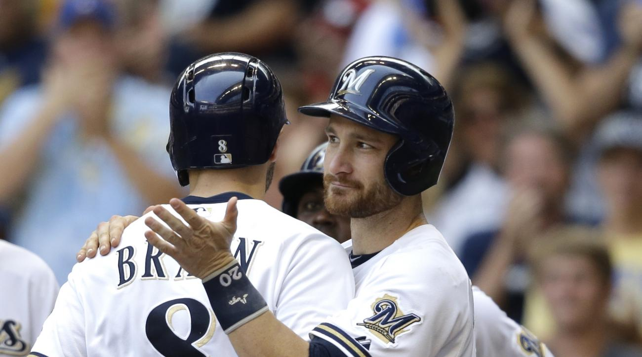 Milwaukee Brewers' Ryan Braun gets a hug from Jonathan Lucroy after his grand slam against the  Philadelphia Phillies during the fifth inning of a baseball game Sunday, Aug. 16, 2015, in Milwaukee. (AP Photo/Jeffrey Phelps)