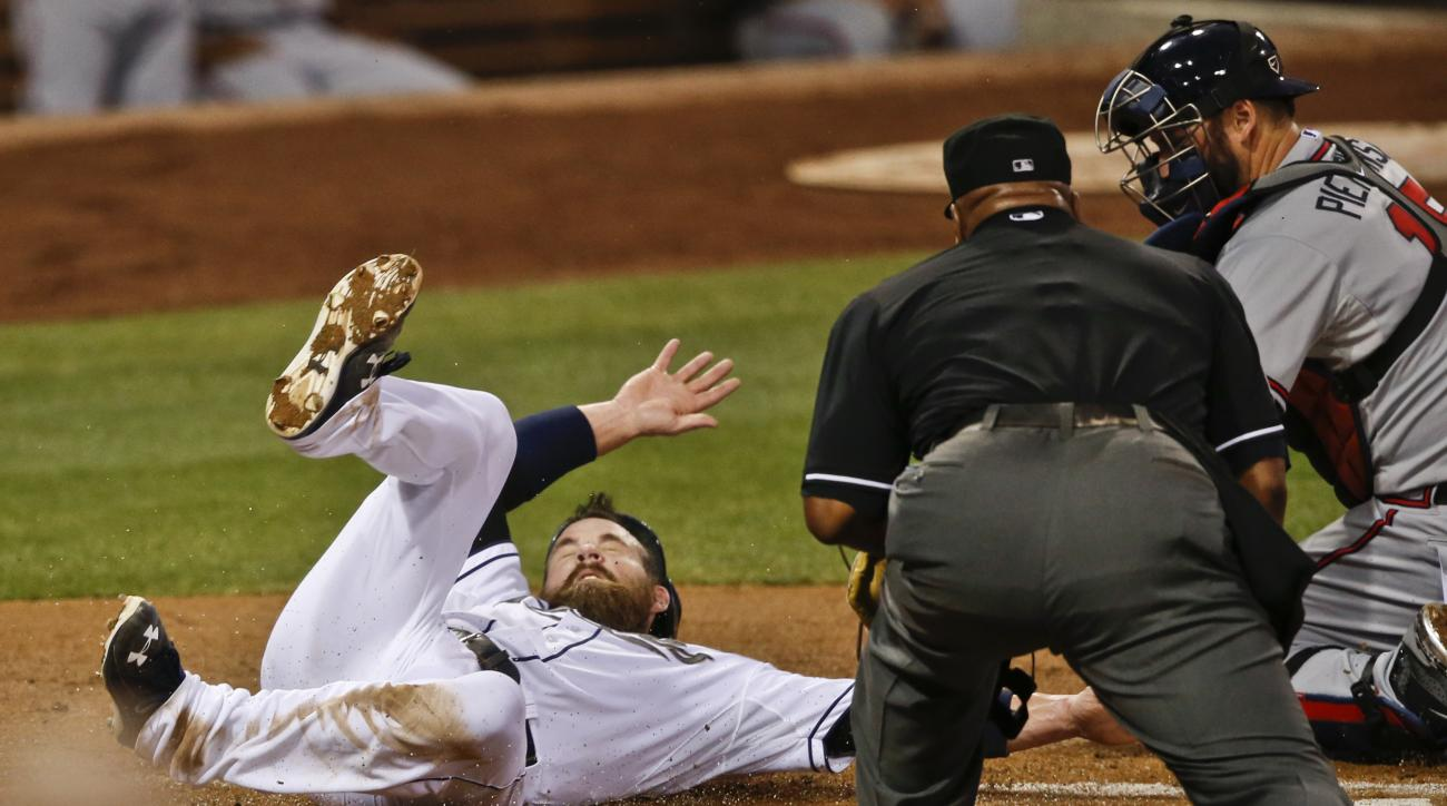 San Diego Padres' Derek Norris, left, is safe at home as umpire Laz Diaz, center, watches a late tag from Atlanta Braves catcher A.J. Pierzynski, right, in the second inning of a baseball game  Monday, Aug. 17, 2015, in San Diego. (AP Photo/Lenny Ignelzi)