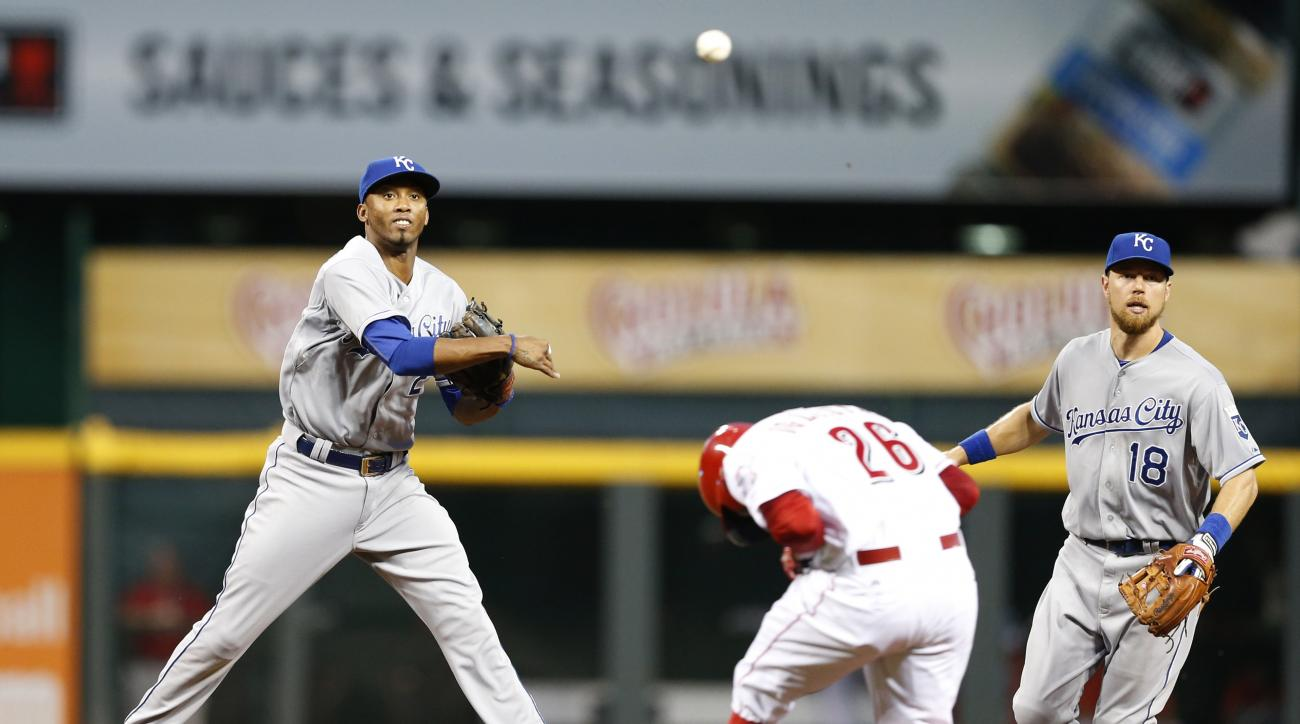 Cincinnati Reds baserunner Raisel Iglesias (26) ducks his head as Kansas City Royals shortstop Alcides Escobar (2) turns a double play during the fifth inning of a baseball game, Tuesday, Aug. 18, 2015, in Cincinnati. At right is Kansas City Royals left f