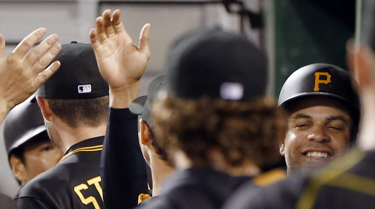 Pittsburgh Pirates' Aramis Ramirez, right, is greeted in the dugout after scoring with Jung Ho Kang on a hit by Pedro Alvarez in the fifth inning of a baseball game against the Arizona Diamondbacks, Tuesday, Aug. 18, 2015, in Pittsburgh. (AP Photo/Keith S