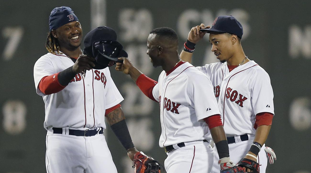 Boston Red Sox outfielders, from left, Hanley Ramirez, Rusney Castillo, and Mookie Betts celebrate after the Red Sox defeated the Cleveland Indians 9-1 in a baseball game in Boston, Tuesday, Aug. 18, 2015. (AP Photo/Michael Dwyer)