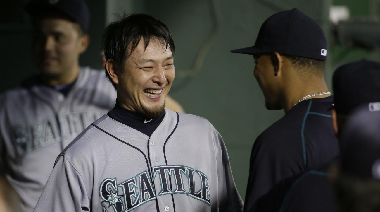 Seattle Mariners starting pitcher Hisashi Iwakuma, of Japan, laughs with teammates in the dugout after the seventh inning of a baseball game against the Texas Rangers in Arlington, Texas, Tuesday, Aug. 18, 2015. (AP Photo/LM Otero)