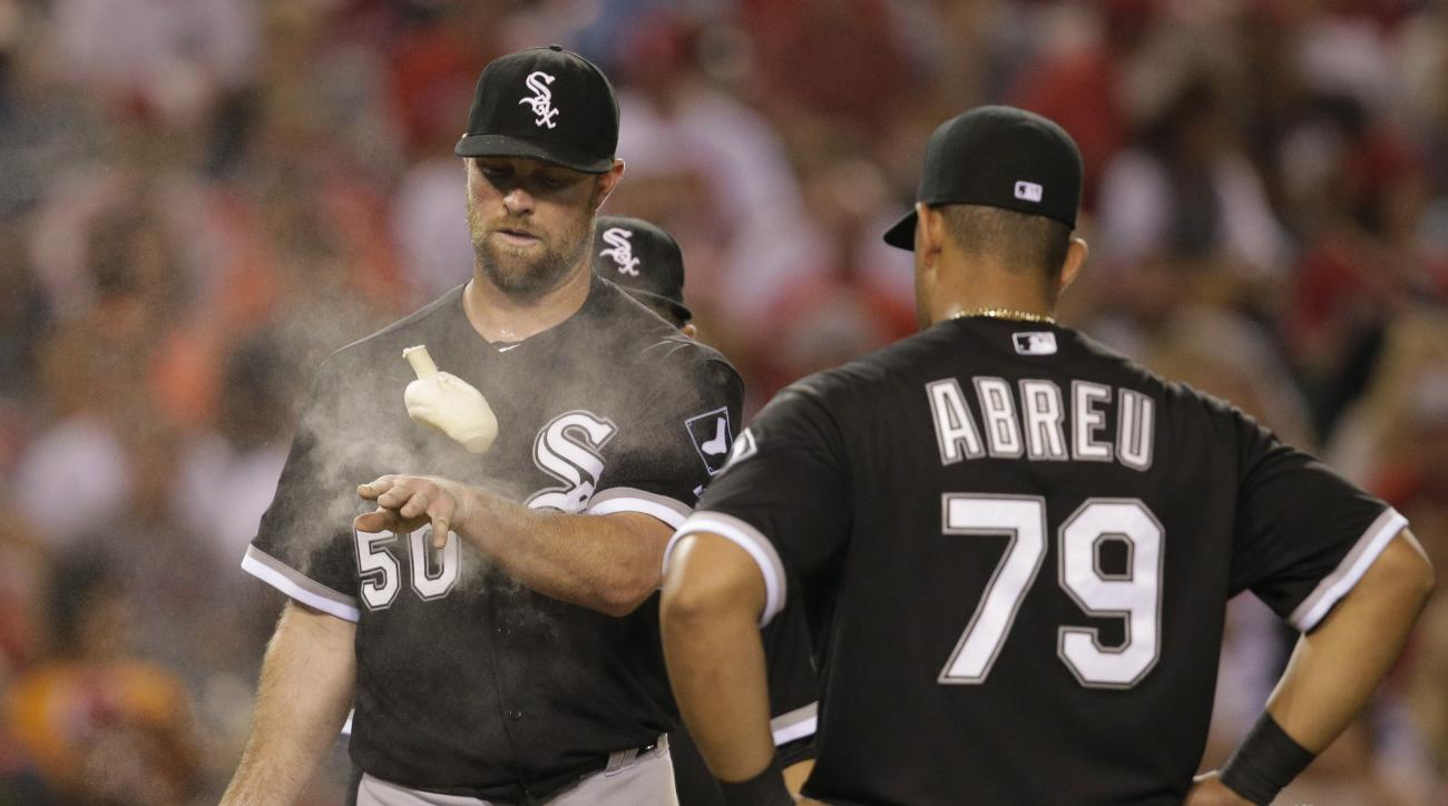 Chicago White Sox starting pitcher John Danks (50) tosses a rosin bag as he is approached by teammates, including first baseman Jose Abreu, during the seventh inning of a baseball game against the Los Angeles Angels, Tuesday, Aug. 18, 2015, in Anaheim, Ca