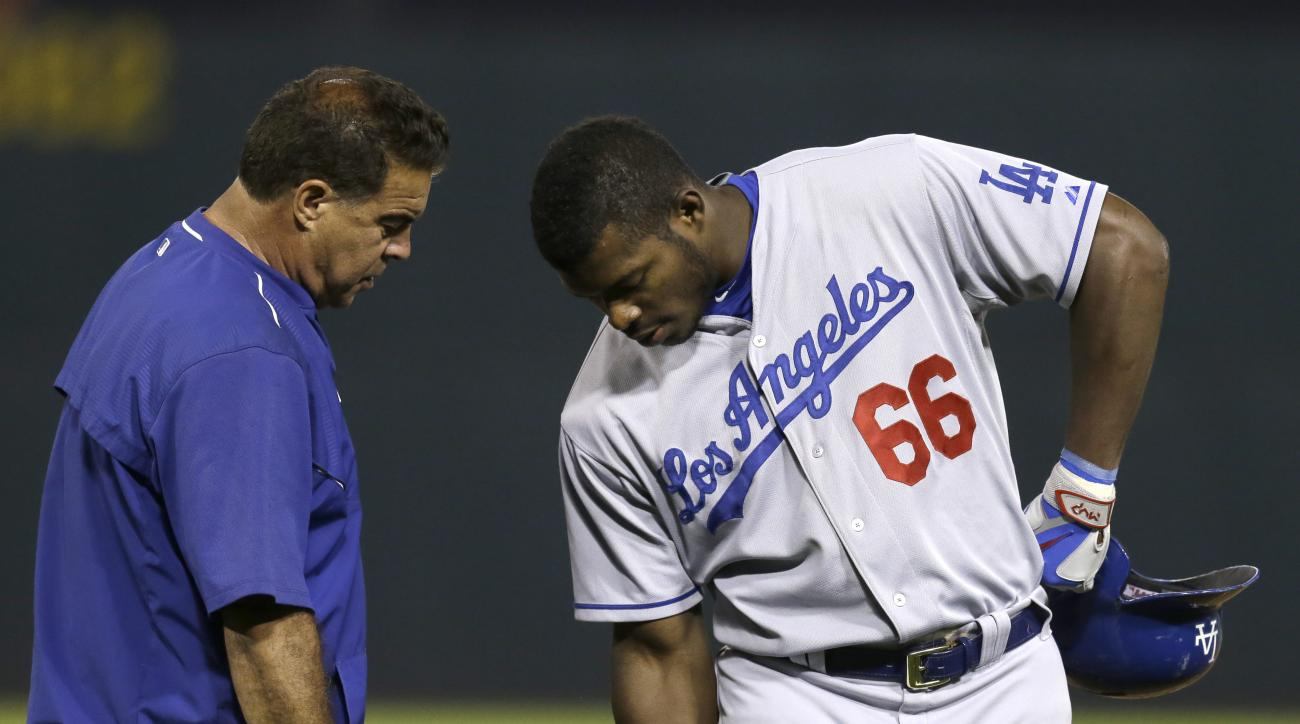 Los Angeles Dodgers' Yasiel Puig (66) is examined by a trainer in the eighth inning of a baseball game against the Oakland Athletics, Tuesday, Aug. 18, 2015, in Oakland, Calif. Puig left the game with an injury. (AP Photo/Ben Margot)