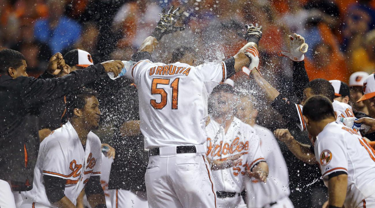 Baltimore Orioles' Henry Urrutia (51) celebrates with teammates as he crosses home plate after hitting a solo home run in the ninth inning of a baseball game against the New York Mets, Wednesday, Aug. 19, 2015, in Baltimore. Baltimore won 5-4. (AP Photo/P