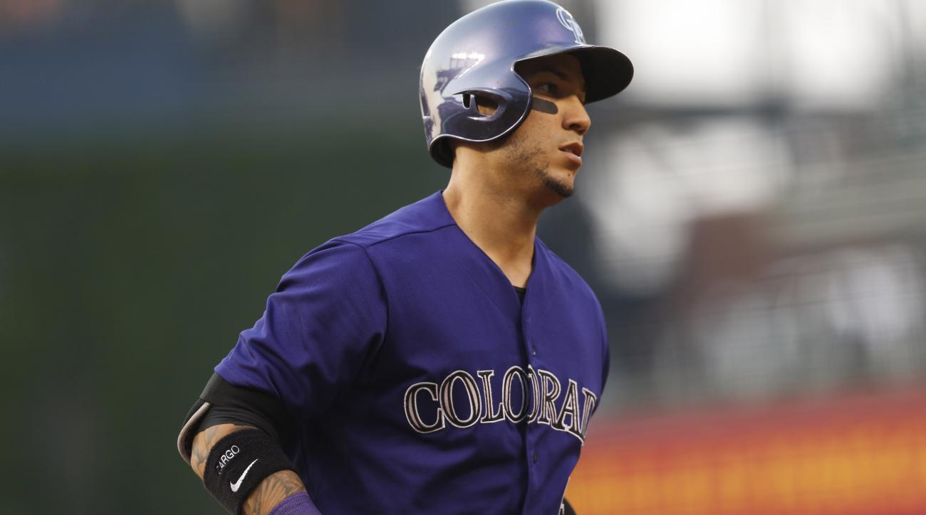 Colorado Rockies' Carlos Gonzalez heads to first base after drawing a walk from Washington Nationals starting pitcher Max Scherzer during the first inning of a baseball game Thursday, Aug. 20, 2015, in Denver. (AP Photo/David Zalubowski)