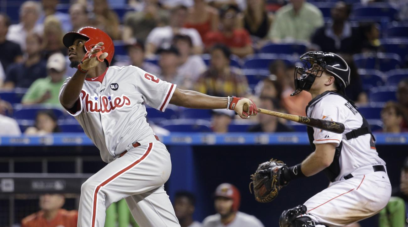 Philadelphia Phillies' Darnell Sweeney, left, pops out to second during the fifth inning of a baseball game against the Miami Marlins, Thursday, Aug. 20, 2015, in Miami. At right is Marlins catcher J.T. Realmuto. (AP Photo/Lynne Sladky)