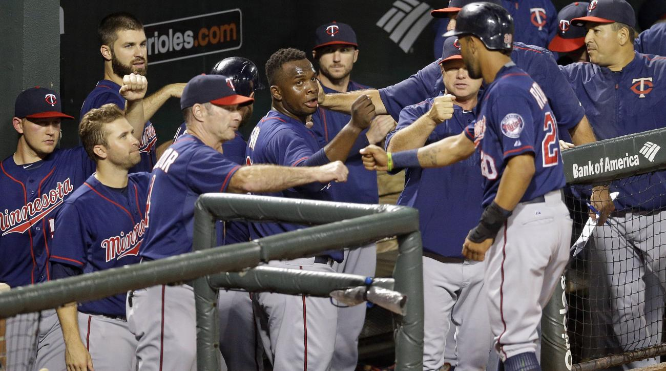 Teammates greet Minnesota Twins' Eddie Rosario, right, as he enters the dugout after scoring on a single by Kurt Suzuki in the second inning of a baseball game against the Baltimore Orioles, Thursday, Aug. 20, 2015, in Baltimore. (AP Photo/Patrick Semansk