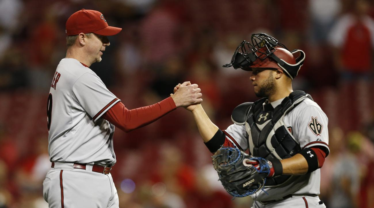 Arizona Diamondbacks relief pitcher Brad Ziegler, left, and catcher Welington Castillo celebrate their 5-4 win over the Cincinnati Reds in a baseball game, Thursday, Aug. 20, 2015, in Cincinnati. (AP Photo/Gary Landers)