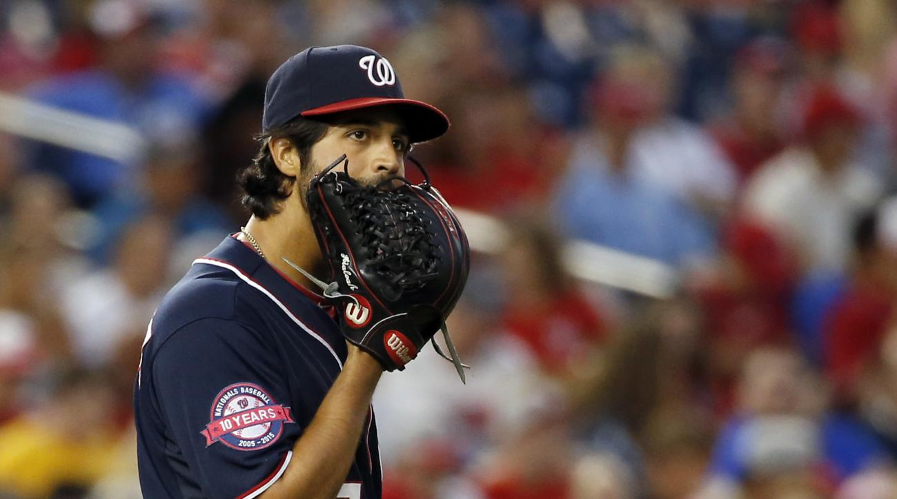 Washington Nationals starting pitcher Gio Gonzalez bites his glove during the third inning of a baseball game against the Milwaukee Brewers at Nationals Park, Friday, Aug. 21, 2015, in Washington. (AP Photo/Alex Brandon)