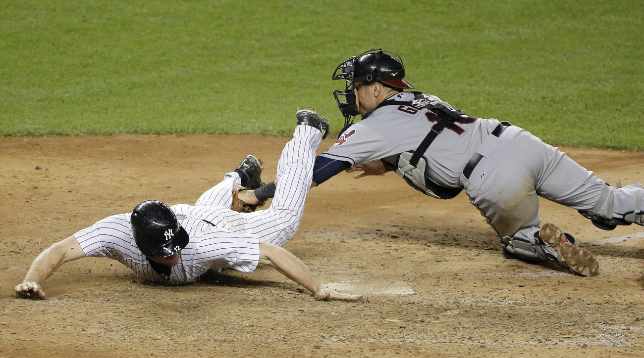 New York Yankees' Chase Headley, left, slides safely across the plate ahead of the tag from Cleveland Indians catcher Yan Gomes during the eighth inning of a baseball game, Friday, Aug. 21, 2015, in New York. Headley scored from second base on a fielding