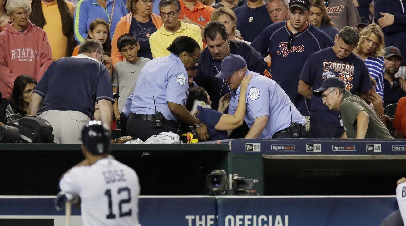 A fan is helped into a stretcher after being hit with a foul ball off the bat of Detroit Tigers' Anthony Gose, foreground, during the eighth inning of a baseball game against the Texas Rangers at Comerica Park Friday, Aug. 21, 2015, in Detroit. (AP Photo/