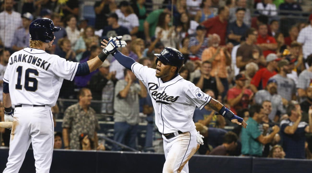 San Diego Padres' Alexi Amarista high-fives with Travis Jankowski, left, as he scores against the St. Louis Cardinals during the fifth inning of a baseball game Friday, Aug. 21, 2015, in San Diego. (AP Photo/Lenny Ignelzi)