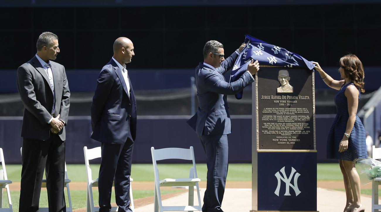 Former New York Yankees catcher Jorge Posada, third from left, and his wife Laura Posada, unveil Posada's plaque that will hang at Monument Park as former teammates Andy Pettitte, far left, and Derek Jeter look on before a baseball game against the Clevel