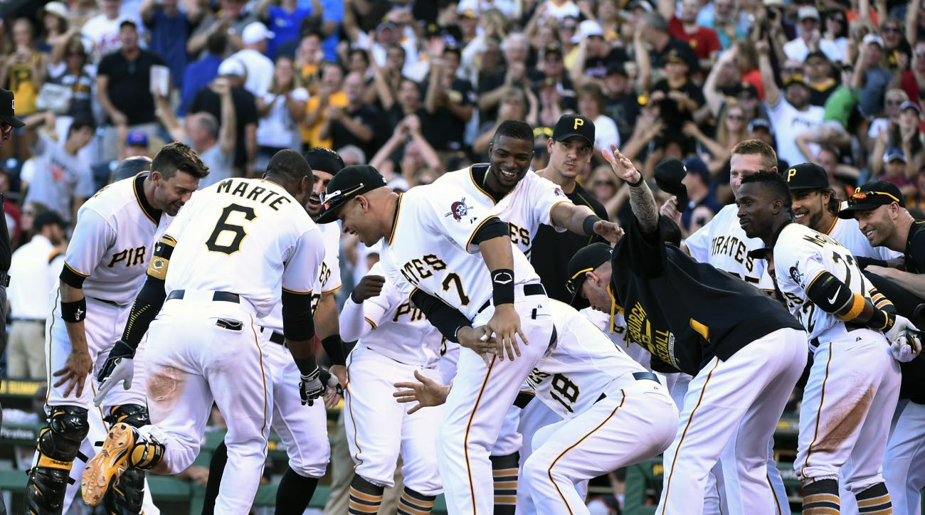 Pittsburgh Pirates' Starling Marte (6)  is greeted by his teammates after hitting a bottom-of-the-ninth baseball game-winning home run off of San Francisco Giants' pitcher George Kontos Saturday, Aug. 22, 2015, in Pittsburgh. (AP Photo/Fred Vuich)