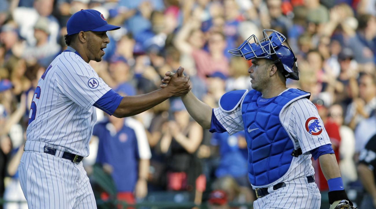 Chicago Cubs catcher Miguel Montero, right, celebrates with closer Hector Rondon after the Cubs defeated the Atlanta Braves 9-7 in a baseball game Saturday, Aug. 22, 2015, in Chicago. (AP Photo/Nam Y. Huh)