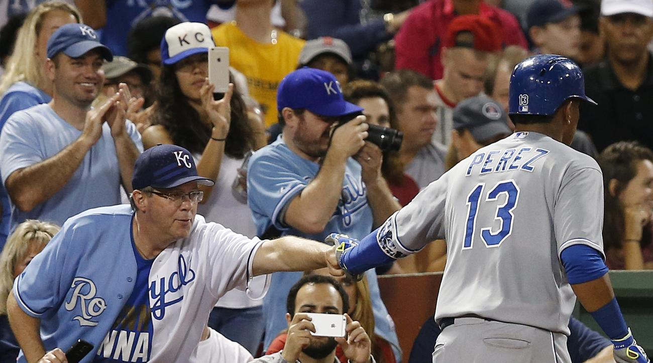 Kansas City Royals' Salvador Perez (13) celebrates his three-run home run with a fan during the sixth inning of a baseball game against the Boston Red Sox in Boston, Saturday, Aug. 22, 2015. (AP Photo/Michael Dwyer)