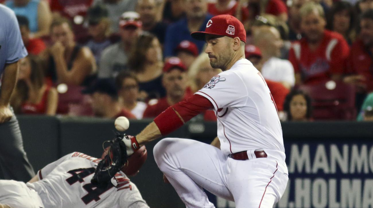 Cincinnati Reds Joey Votto misses the throw allowing Arizona Diamondbacks Paul Goldschmidt to dive back safely to first base in the fourth inning of their baseball game in Cincinnati, Saturday, Aug. 22, 2015. (AP Photo/Tom Uhlman)