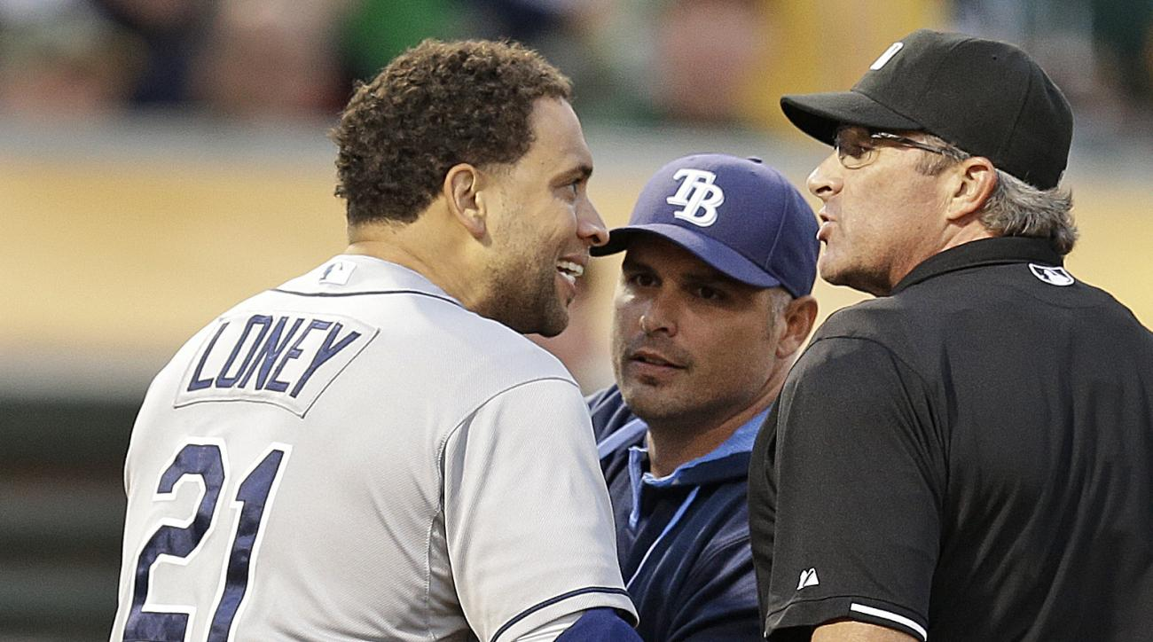 Tampa Bay Rays' James Loney (21) is restrained by manager Kevin Cash, center, while arguing with home plate umpire Paul Nauert, right,after being ejected in the sixth inning of a baseball game against the Oakland Athletics, Saturday, Aug. 22, 2015, in Oak