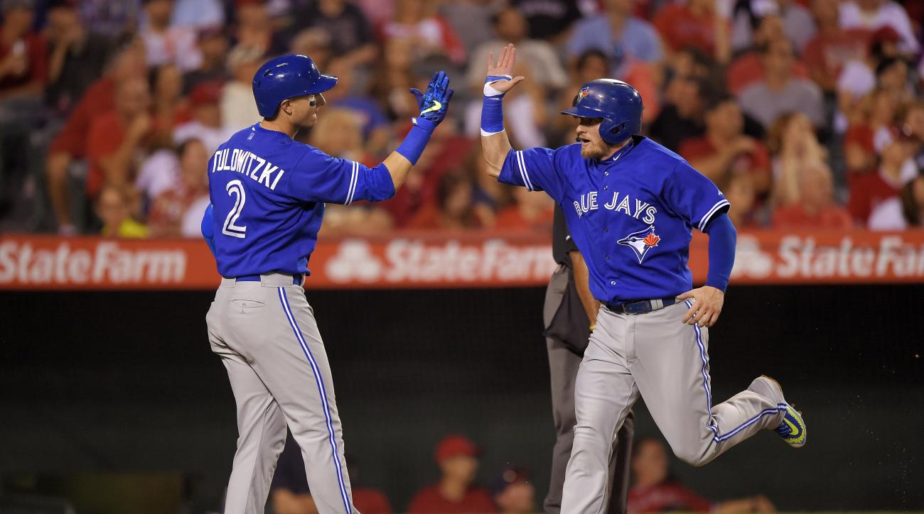 Toronto Blue Jays' Josh Donaldson, right, is congratulated by Troy Tulowitzki after scoring on a triple by Jose Bautista during the fourth inning of a baseball game, Saturday, Aug. 22, 2015, in Anaheim, Calif. (AP Photo/Mark J. Terrill)