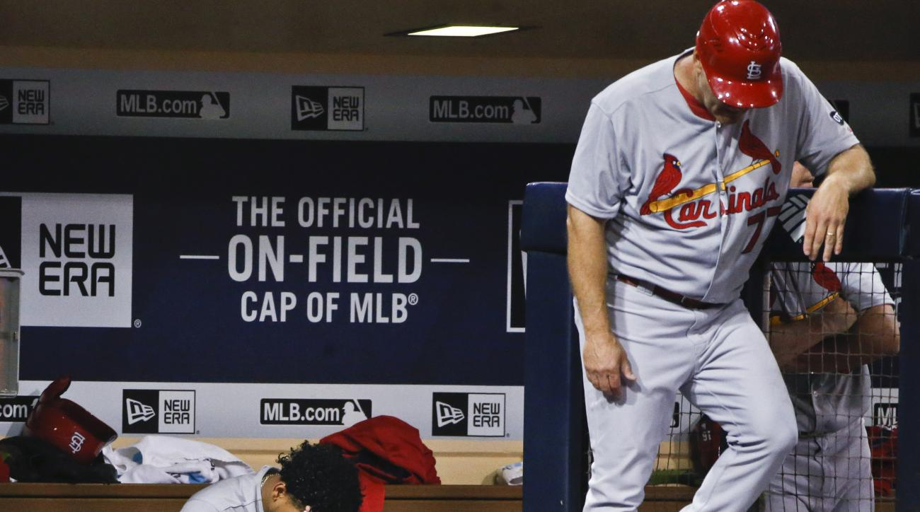 St. Louis Cardinals starting pitcher Carlos Martinez holds his head as he sits in the dugout during a seven-run rally by the San Diego Padres during the seventh inning of a baseball game Saturday, Aug. 22, 2015, in San Diego. (AP Photo/Lenny Ignelzi)