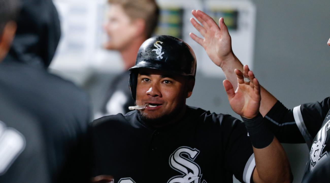 Chicago White Sox's Melky Cabrera is congratulated after scoring on a passed ball in the 10th inning of Chicago's 6-3 win over the Seattle Mariners during a baseball game Saturday, Aug. 22, 2015, in Seattle. (AP Photo/John Froschauer)