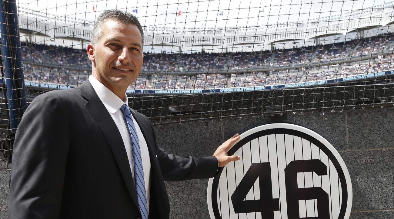 Retired New York Yankees pitcher Andy Pettitte touches his plaque in Yankee Stadium's Monument Park during a pregame ceremony retiring his number before a baseball game in New York, Sunday, Aug. 23, 2015.  The Yankees will retire Pettitte's No. 46 on Sund