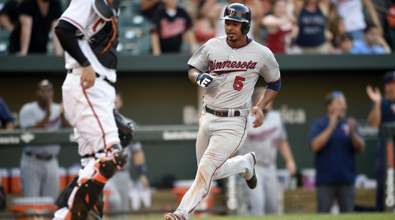 Minnesota Twins' Eduardo Escobar runs home to score during the 12th inning of a baseball game as Baltimore Orioles catcher Caleb Joseph waits, Sunday, Aug. 23, 2015, in Baltimore. The Twins' Shane Robinson reached first on a fielding error by Orioles' Jim