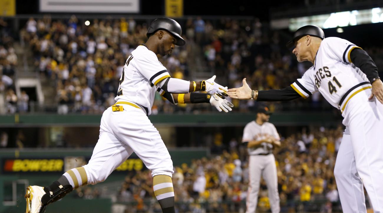 Pittsburgh Pirates' Andrew McCutchen, left, is greeted by third base coach Rick Sofield (41) after hitting a solo home run off San Francisco Giants relief pitcher Jeremy Affeldt, center, during the sixth inning of a baseball game, Sunday, Aug. 23, 2015, i