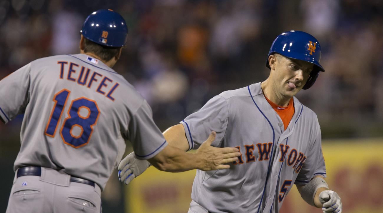 New York Mets' David Wright, right, passes third base coach Tim Teufel, left, while scoring on a home run by Wilmer Flores in the fourth inning of a baseball game with the Philadelphia Phillies, Monday, Aug. 24, 2015, in Philadelphia. (AP Photo/Laurence K