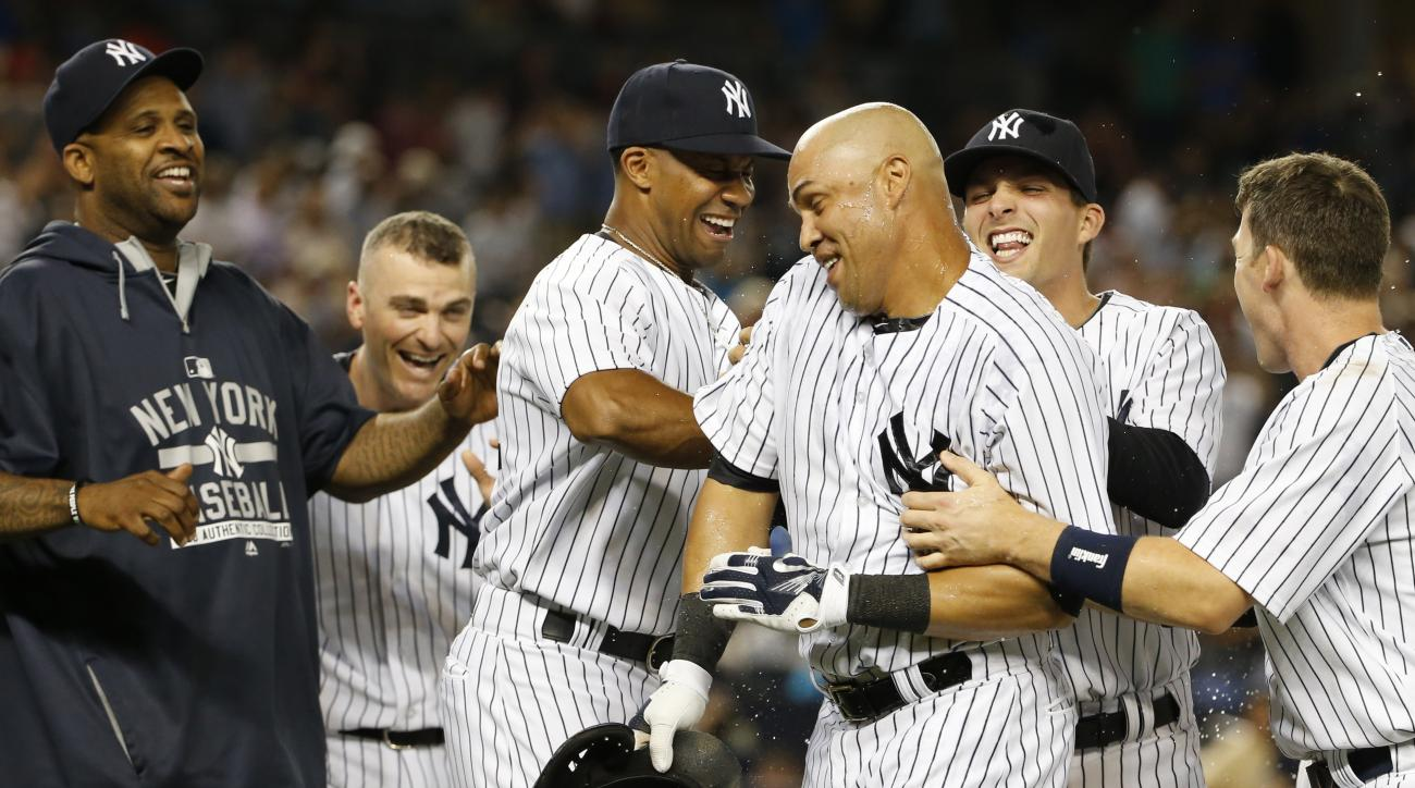 New York Yankees teammates celebrate with New York Yankees Carlos Beltran, third from right, after he hit a ninth-inning, walk-off, sacrifice fly allowing New York Yankees Brett Gardner to score in the Yankees 1-0 victory over the Houston Astros in a base