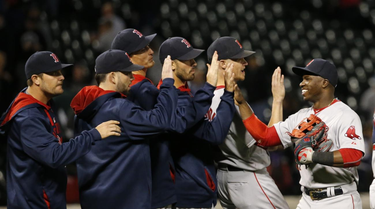 Boston Red Sox right fielder Rusney Castillo, right, celebrates with his teammates the Red Sox's 5-4 win over the Chicago White Sox after a baseball game Monday, Aug. 24, 2015, in Chicago. (AP Photo/Charles Rex Arbogast)