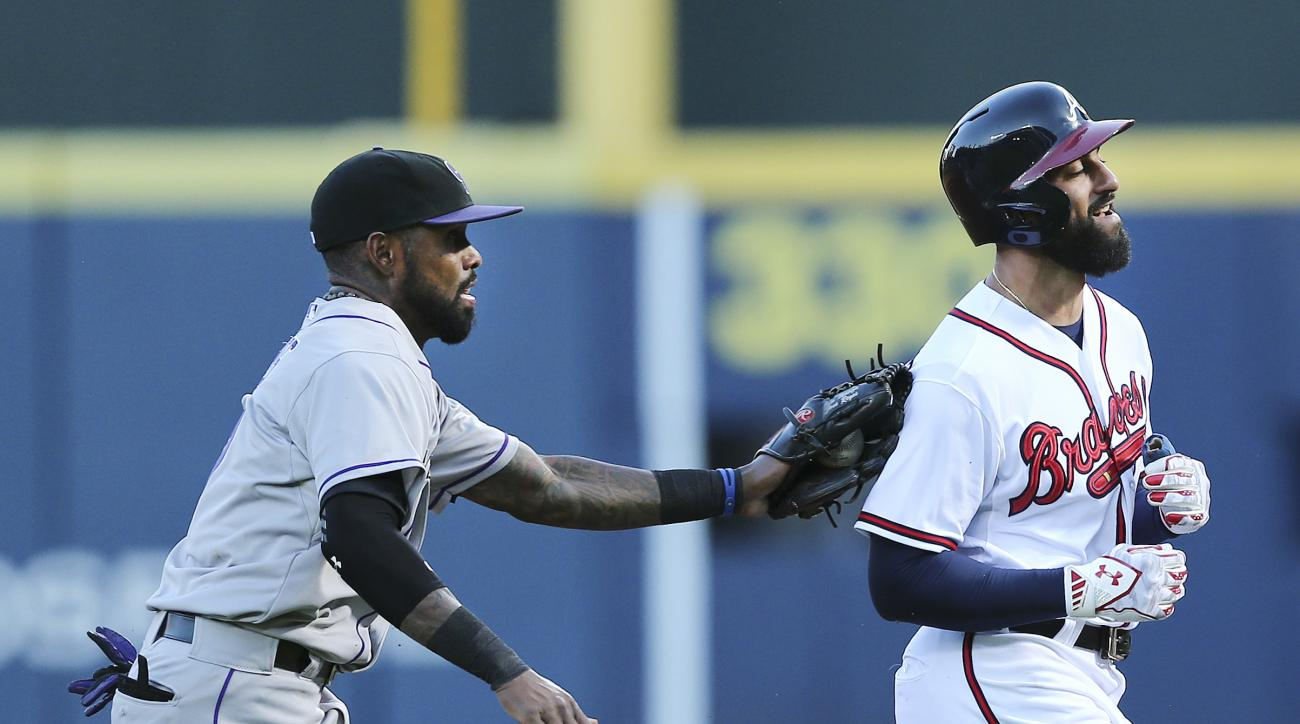 Atlanta Braves' Nick Markakis, right, is tagged out by Colorado Rockies shortstop Jose Reyes (7) after being caught in a rundown in the first inning of a baseball game Tuesday, Aug. 25, 2015, in Atlanta. (AP Photo/John Bazemore)
