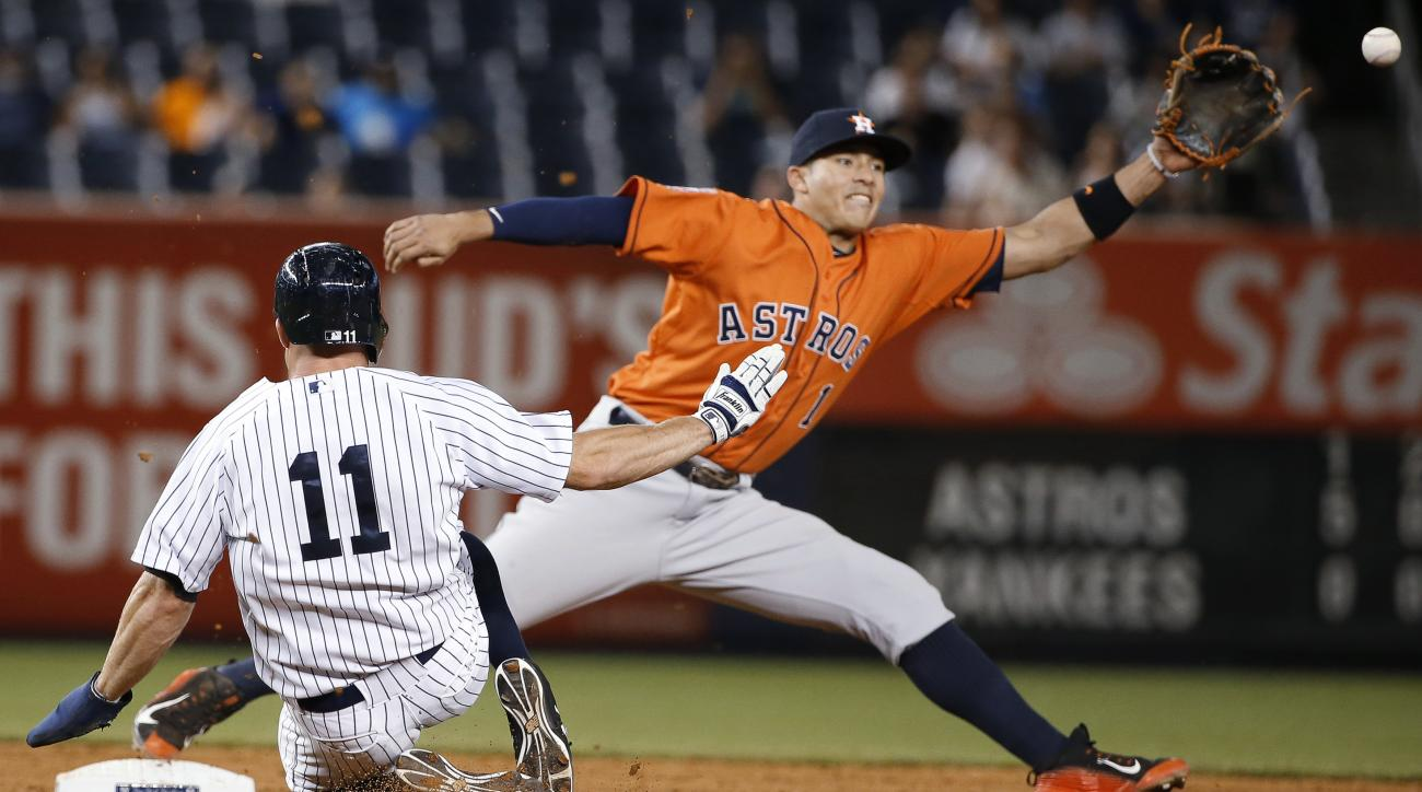 Houston Astros shortstop Carlos Correa (1)  keeps his foot on the bag as he reaches for a wide throw to put out New York Yankees' Brett Gardner on during the ninth inning of the Astros' 15-1 win over the Yankees in a baseball game at Yankee Stadium in New