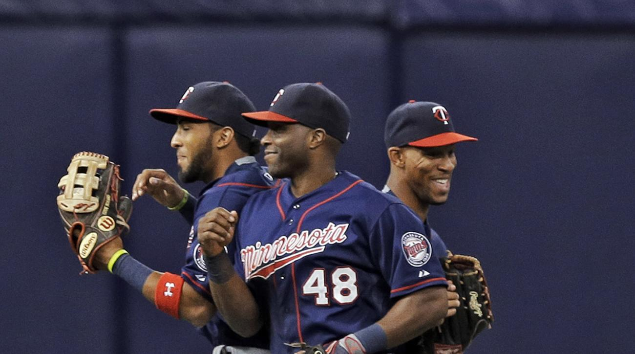 Minnesota Twins, from left, Byron Buxton, Torii Hunter, and Eddie Rosario celebrate the team's 11-7 win over the Tampa Bay Rays during a baseball game Tuesday, Aug. 25, 2015, in St. Petersburg, Fla.  (AP Photo/Chris O'Meara)