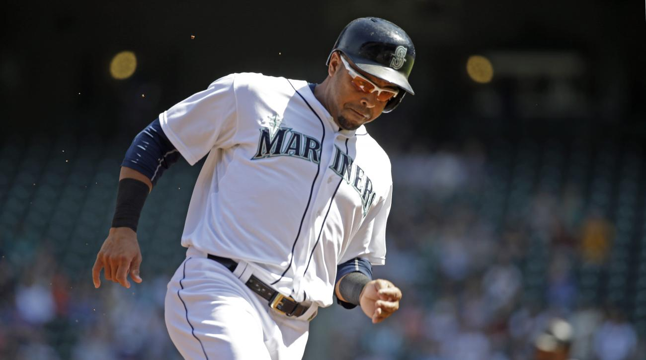 Seattle Mariners' Nelson Cruz, foreground, heads home as Robinson Cano advances to third base on a double by Seth Smith against the Oakland Athletics in the first inning of a baseball game Wednesday, Aug. 26, 2015, in Seattle. (AP Photo/Elaine Thompson)
