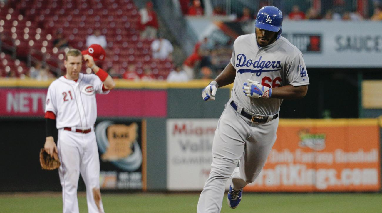 Los Angeles Dodgers' Yasiel Puig rounds third base on a two-run home run as Cincinnati Reds third baseman Todd Frazier (21) watches during the fourth inning of a baseball game, Wednesday, Aug. 26, 2015, in Cincinnati. (AP Photo/John Minchillo)