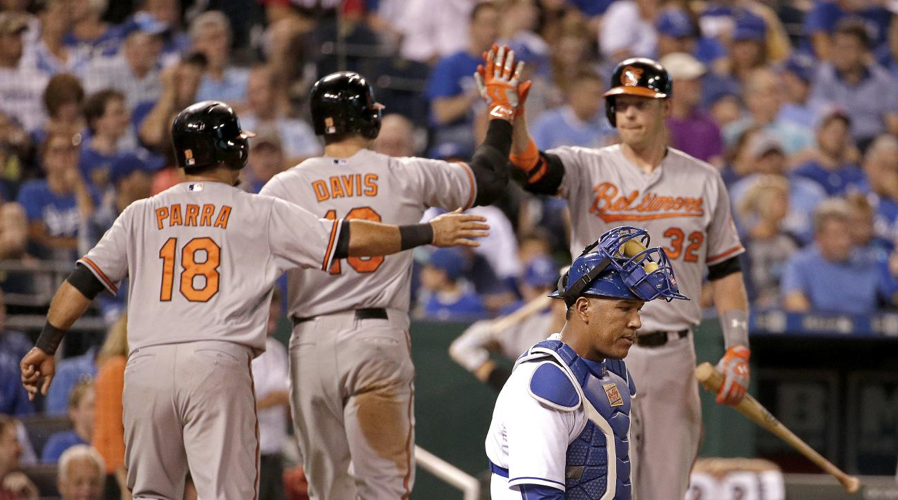 Baltimore Orioles' Chris Davis, center back, celebrates with teammate Gerardo Parra (18) and Matt Wieters (32) after hitting a two-run home run during the fifth inning of a baseball game against the Kansas City Royals, Wednesday, Aug. 26, 2015, in Kansas